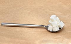 Spoon full with white sugar cubes pile Stock Photos