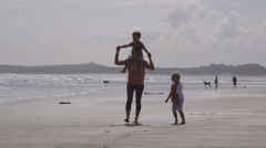 Happy young family of three walk along the water's edge on the beach together Stock Footage