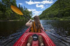 Young woman paddles down river in a kayak, Jacques-Cartier National Park, Stock Photos