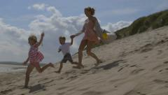 family of three smiles and laughs as they run down a sand dune together. - stock footage