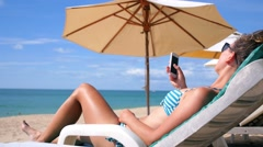 Woman on Beach Using Smart Phone on Vacation - stock footage
