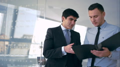 Two handsome businessman discussing document - stock footage