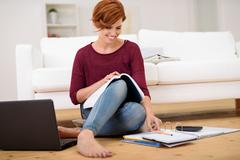 Happy Student Answering Homework at Living Area Stock Photos