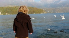 A little blond boy gives bread to the seagulls on the lakefront Stock Footage