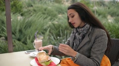 Beautiful woman brunette eating sandwich by hands at outdoor cafe - stock footage