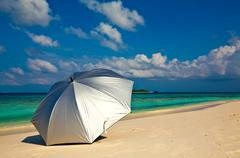 Silvery umbrella is on a sandy beach, Maldives - stock photo