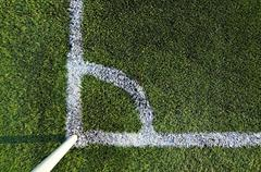 Corner of a football (soccer) field is made from synthetic lawn - stock photo