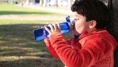 Portrait of a cute child drinking water from a bottle outdoor Arkistovideo