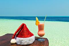 Bocal of drink is on a beach table with Santa hat (Maldives, The Indian Ocean Stock Photos