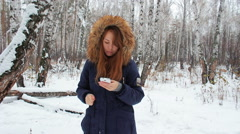 The girl iwalking in the winter woods with phone - stock footage