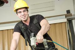 Carpenter at work on job using power tool - stock photo