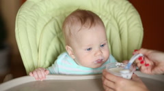 Stock Video Footage of smiling baby eating food on kitchen in his chair