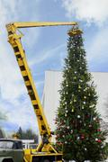 Assembling of the Christmas tree with the crane truck outdoor - stock photo