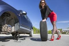 Leggy female changing wheel of car - stock photo