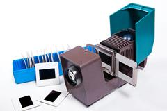 Old projector for displaying of slides. Slides in blue box on white background Stock Photos