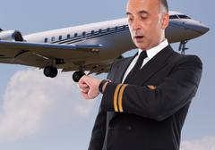 Handsome airline worker looking at his watch - stock photo