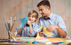 Father and son cutting paper - stock photo