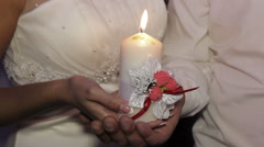 The  bride and groom hold a candle in hands closeup Stock Footage