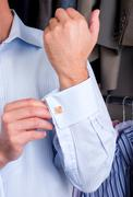 A man putting on his cuff links Stock Photos