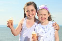 Sister eating ici-cream in front of ocean - stock photo