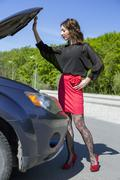 Female driver inspects her car engine - stock photo