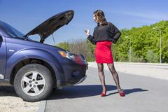 Female driver inspects her car engine Stock Photos
