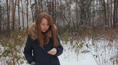 The girl iwalking in the winter woods with phone Stock Footage