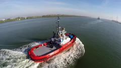 Aerial bird view of a harbor tugboat sailing through a canal without load 4k Stock Footage