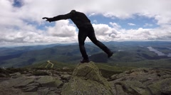 Guy balances on top of mountain Stock Footage