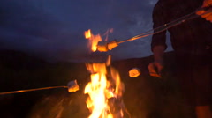 Group roasts marshmallows over fire dolly out - stock footage