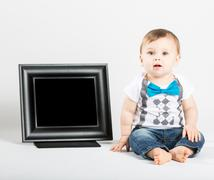 Baby Sitting Next to Picture Frame and Looking at Camera - stock photo