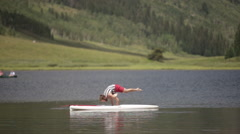 Close up man does yoga on paddle board in mountain lake - stock footage