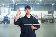 Smiling repairman with tire wrench. Stock Photos