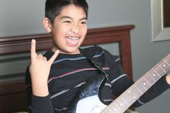 Asian boy play guitar in his bedroom Stock Photos