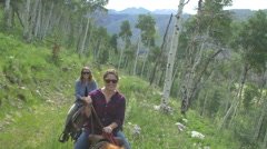 4k Young women ride horses through aspen trees in colroado - stock footage