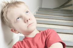 Stock Photo of Neglected lonely child leaning at the wall
