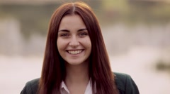 Close-up of attractive teenage girl smiling at camera outdoor Stock Footage