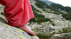 Beautiful view of a mountain lake, barefooted woman sitting on a rock Stock Footage
