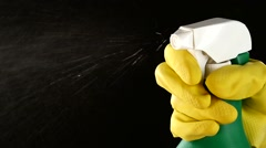 Hand in glove holds spray bottle, on black, slow motion, close up - stock footage