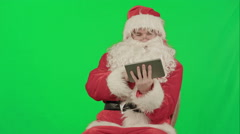 Santa listening music and touching tablet on a Green Screen Chrome Key Stock Footage