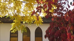 Yellow and red tree leaves in front of church house Stock Footage