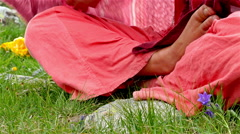 Woman in orange clothes sitting on the meadow cross-legged and with bare feet - stock footage