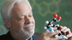 Portrait of a Chemistry Professor looking at a model of a molecule, close up Stock Footage
