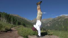 4k Man does handstand with scenic mountain back drop Stock Footage