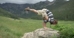 4k Man does yoga on rock in Colorado mountain valley - stock footage