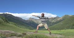 4k Man does yoga to reveal a Colorado mountain valley - stock footage