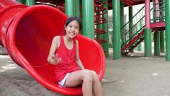 Happy Asian child playing on a slide in playground Stock Footage
