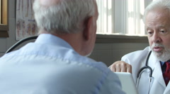 A Physician advising a senior male patient about pills - stock footage