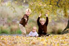Three Young Children playing in Fallen Leaves - stock photo