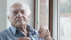4K Portrait of sad elderly man sitting by the window Stock Footage